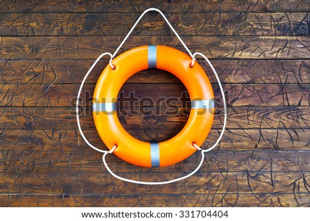 A life buoy on wooden background - stock photo