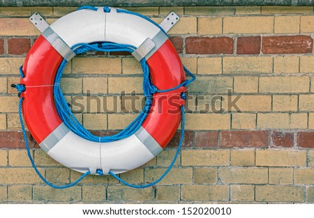 A Lifebuoy Attached to a Stone Wall  - stock photo