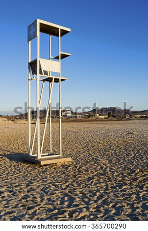 A lifeguard station at the beach in the warm late afternoon sun against blue sky. - stock photo