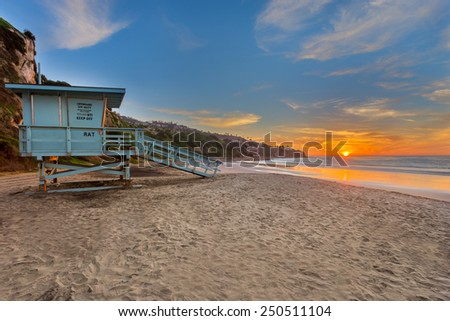 A lifeguard tower on the beach at sunset. - stock photo