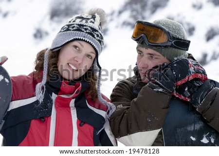 A lifestyle image of two teens snowboarders in winter outdoors - stock photo