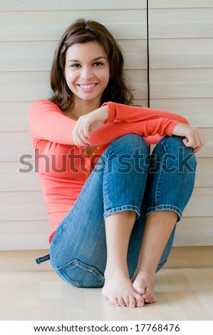 A lifestyle shot of an attractive young woman sitting on the floor