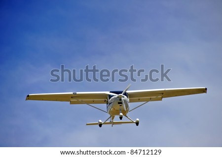 A light aircraftat the moment of landing. Space for text in the sky. - stock photo