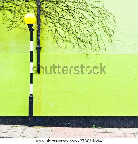 A light at a zebra crossing in front of a green wall in London, UK - stock photo