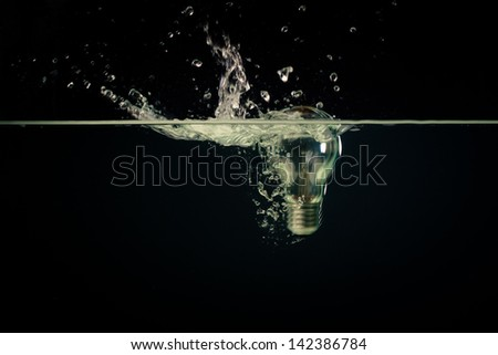A light bulb falling into clear water with dark background - stock photo