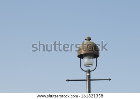 A light on top of a long metal pole. - stock photo