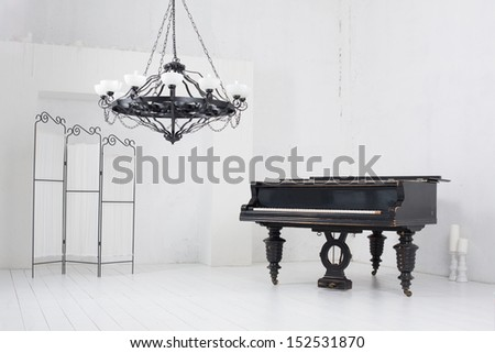 A light room with a piano, a folding screen and a chandelier - stock photo