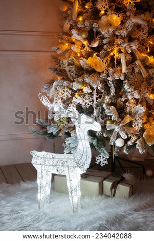 A lighted Christmas tree with deer underneath. - stock photo