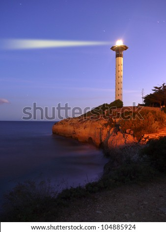 A lighthouse at dusk. Picture taken near Tarragona, Spain. - stock photo