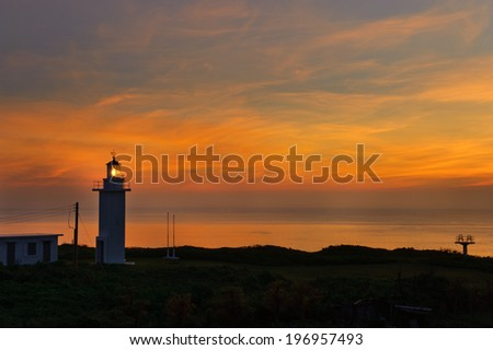 A lighthouse facing the water during the sunset.