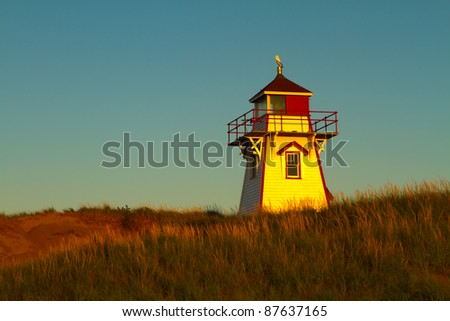 A lighthouse in Prince Edward Island national park, PEI, Canada. Lit by the setting sun. - stock photo