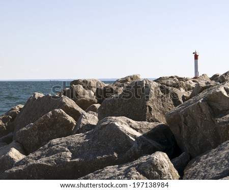 A lighthouse perched on a set of rocks on the water.