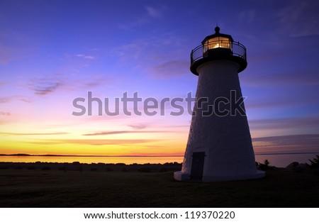 A lighthouse silhouette at sunrise along the New England coastline. - stock photo