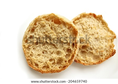 A lightly toasted English Muffin on white.                                - stock photo