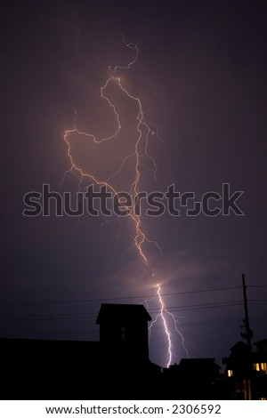 A lightning bolt shaped like a heart strikes a residential area. A great card for Valentine's Day. - stock photo