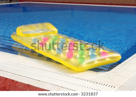 a lilo or inflatable air bed on the side of a swimming pool