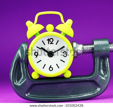 A lime green alarm clock placed in a Grey clamp against a pastel purple background, asking the question do you manage your time effectively. - stock photo