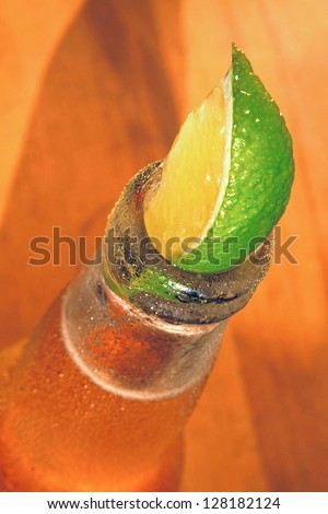 A Lime in a bottle of lager - stock photo