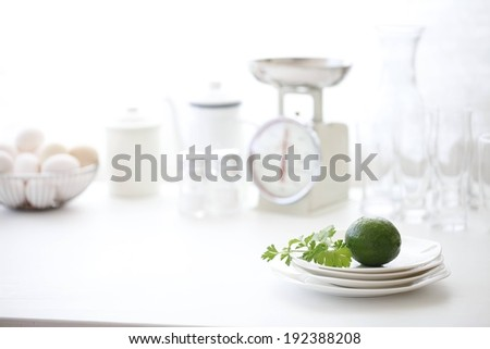 A lime on plates with a scale and eggs with other dishes in the background. - stock photo