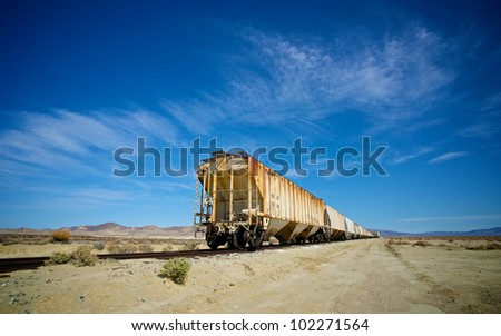 A line of abandoned train cars stand on railroad tracks near Death Valley National Park. - stock photo