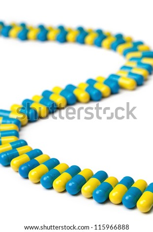 A line of blue and yellow pills curving in and out isolated on a white background.