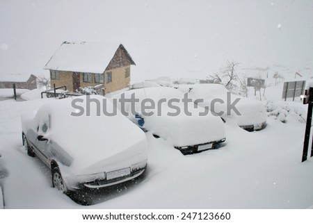 A line of cars buried under snow drifts during a blizzard. - stock photo
