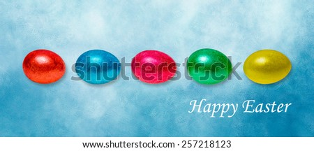 A line of colorful Easter eggs of red, blue, green, yellow and orange color against textured blue background and a text  Happy Easter! Panoramic format image