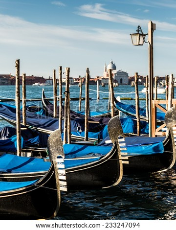 A line of empty gondolas parked along the waterfront in Venice, Italy - stock photo