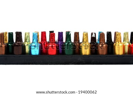 A line of liquor chocolates in the shape of a bottle wrapped in colorful papers.