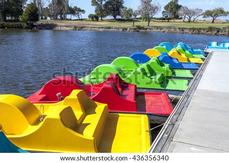 A line of paddle boats docked on the pier. - stock photo