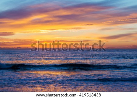 A line of surfers wait for the last waves of the day during sunset over the ocean. - stock photo