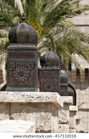 A line of traditional Arabian lanterns or lamps against an Arabic backdrop. - stock photo