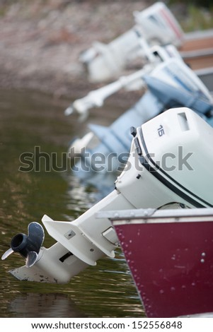 a line up of outboard motors on a lake - stock photo