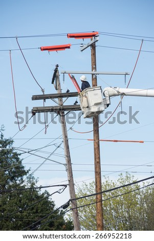 A lineman high in a truck bucket works to repair electric lines. - stock photo