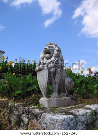 A lion statue at a Jamaican plantation estate. - stock photo