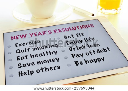 a list of new years resolutions in a tablet, on a table with a cup of coffee and a glass with orange juice - stock photo