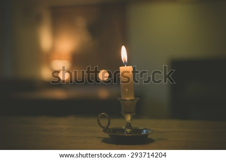 A lit candle on a table in a dining room - stock photo