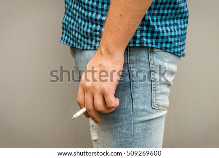 A lit cigarette in the man's hand. Horizontal photo.