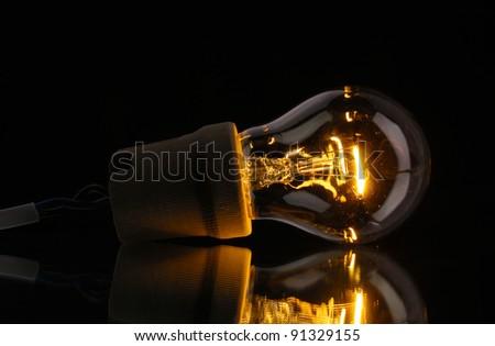 A lit light bulb on black background - stock photo