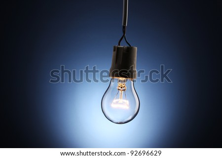 A lit light bulb on blue background