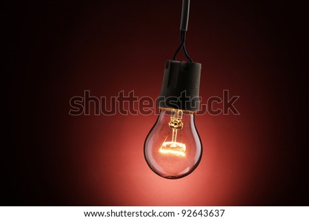 A lit light bulb on red background