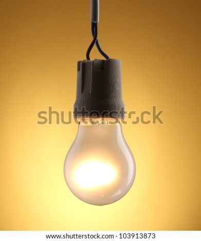 A lit light bulb on yellow background