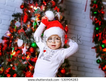 A little adorable girl in red santa's suit in a christmas decoration having fun . Cute children with toys indoors near xmas tree smiling. New year photo.