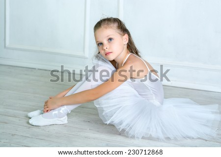 A little adorable young ballerina in a playful mood in the interior studio posing on camera - stock photo