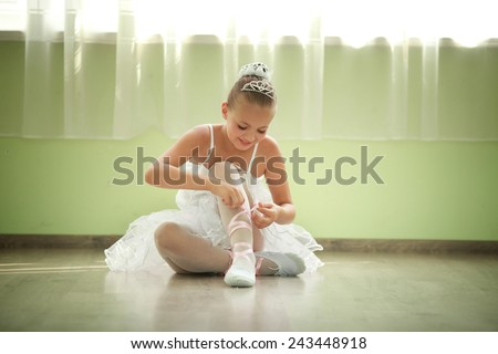 A little adorable young ballerina in white ballet dress tutu is  - stock photo