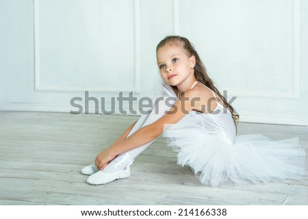 A little adorable young ballerina in white ballet dress tutu is sitting on floor in the interior studio