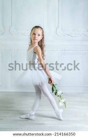 A little adorable young ballerina is posing with eustoma flowers on camera in the interior studio  - stock photo