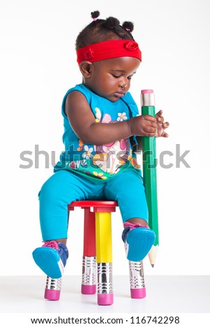 A little African baby with a huge pencil in the hands. - stock photo