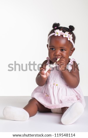 A little African baby with a sticky mashmallow. - stock photo