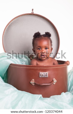 A little African girl in a hat case on a light turquoise organza. - stock photo